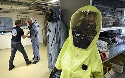 A man tries on an air permeable charcoal impregnated suit, combined with a respirator (or gas mask), rubber boots and three layers of gloves during a simulation at the OPCW (The Organisation for the Prohibition of Chemical Weapons) headquarters in The Hague, The Netherlands, on April 20, 2017.  ( AFP PHOTO / JOHN THYS)