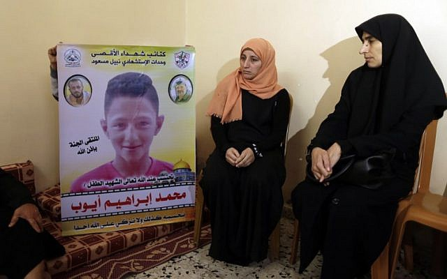 The mother (C) of 15-year-old Palestinian Mohammed Ayoub, who was shot and killed by Israeli security forces during clashes along the Israel-Gaza border, sits as another person raises his portrait, among other relatives as they mourn in their home in Beit Lahia in the northern Gaza Strip on April 21, 2018 (AFP PHOTO / MAHMUD HAMS)