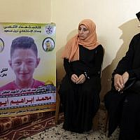 The mother (C) of 15-year-old Palestinian Mohammed Ibrahim Ayoub, who was reportedly shot and killed by the IDF during clashes along the Israel-Gaza border, sits as another person raises his portrait, among other relatives as they mourn in their home in Beit Lahia in the northern Gaza strip on April 21, 2018. (AFP PHOTO / MAHMUD HAMS)