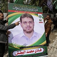 A picture taken on April 21, 2018 shows men holding up a poster portrait of 35-year-old Palestinian professor and Hamas member Fadi Mohammad al-Batsh who was killed in Malaysia, outside his family's house in Jabaliya in the northern Gaza strip.  (AFP PHOTO / MAHMUD HAMS)