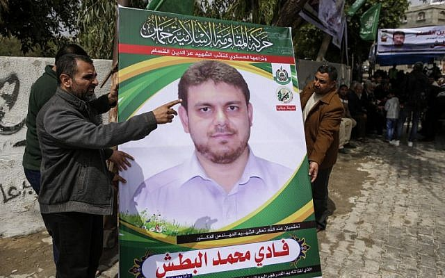 A picture taken on April 21, 2018 shows men holding up a poster portrait of 35-year-old Palestinian professor and Hamas member Fadi Mohammad al-Batsh who was killed in Malaysia, outside his family's house in Jabalia in the northern Gaza strip.  (AFP PHOTO / MAHMUD HAMS)