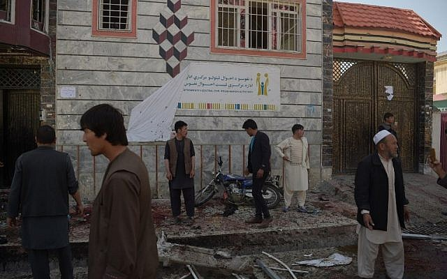 Afghan residents inspect the site of a suicide bombing outside a voter registration center in Kabul on April 22, 2018. (AFP PHOTO / SHAH MARAI)