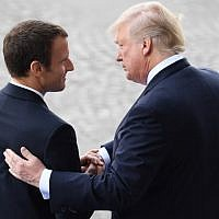In this file photo taken on July 14, 2017, French President Emmanuel Macron (L) bids farewell to his US counterpart Donald Trump after the annual Bastille Day military parade on the Champs-Elysees avenue in Paris. (AFP Photo/Alain Jocard)