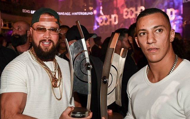 Picture taken on April 12, 2018 in Berlin shows German rappers Kollegah (L) and Farid Bang posing with their Echo trophies they were given in the 2018 Hip-Hop/Urban category. (AFP PHOTO / dpa / Jens Kalaene0