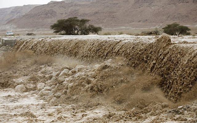 A general view of flooded water running through a valley blocking the main road along the Dead Sea, near the desert fortress of Masada, following heavy rainfall on April 25, 2018. (AFP Photo/Menahem Kahana)