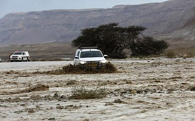 A car drives through flooded water running through a valley blocking the main road along the Dead Sea, near the desert fortress of Masada, following heavy rainfall on April 25, 2018. (AFP Photo/Menahem Kahana)