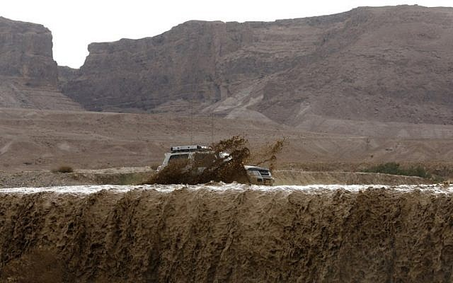 Illustrative: A car drives through flooded water running through a valley blocking the main road along the Dead Sea, near the desert fortress of Masada, following heavy rainfall on April 25, 2018. (AFP Photo/Menahem Kahana)