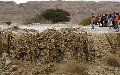Israelis watch flooded water running through a valley blocking the main road along the Dead Sea in the Judean desert, near the desert fortress of Masada north of Ein Bokek, following heavy rainfall in the mountains on April 25, 2018. (AFP PHOTO / MENAHEM KAHANA)