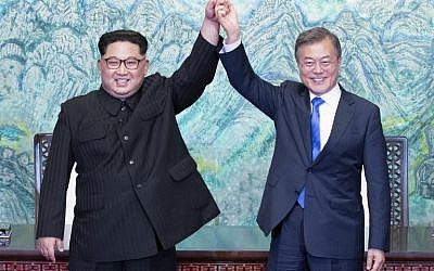 North Korea's leader Kim Jong Un (L) and South Korea's President Moon Jae-in (R) raise their joined hands during a signing ceremony near the end of their historic summit at the truce village of Panmunjom on April 27, 2018. (AFP/Korea Summit Press Pool/Korea Summit Press Pool)