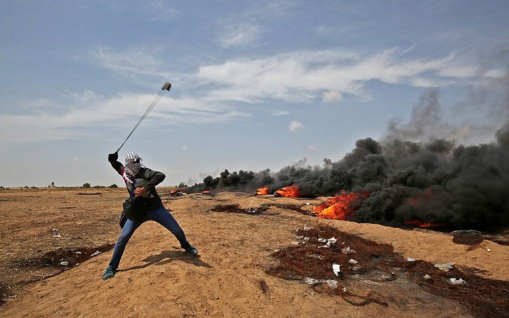 A Palestinian uses a slingshot to hurl stones at Israeli troops near Khan Younis in the southern Gaza Strip, during the fifth straight Friday of mass riots along the border between Gaza and Israel, on April 27, 2018. (AFP Photo/Said Khatib)