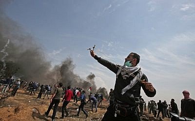 A Palestinian demonstrator uses a slingshot to hurl stones towards Israeli security forces near the southern Gaza Strip town of Khan Younis during the fifth straight Friday of mass demonstrations and clashes along the Gaza-Israel border on April 27, 2018. (AFP Photo/Said Khatib)