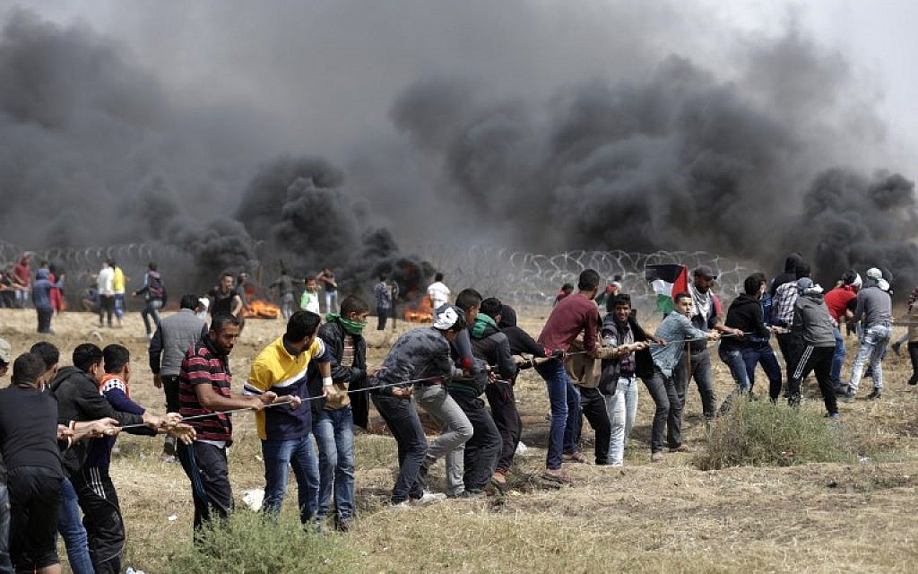 Palestinians try to pull down part of the border fence between Israel and Gaza east of Jabaliya in the northern Gaza Strip,  during the fifth straight Friday of mass riots along the border between Gaza and Israel, on April 27, 2018. (AFP Photo/Mahmud Hams)