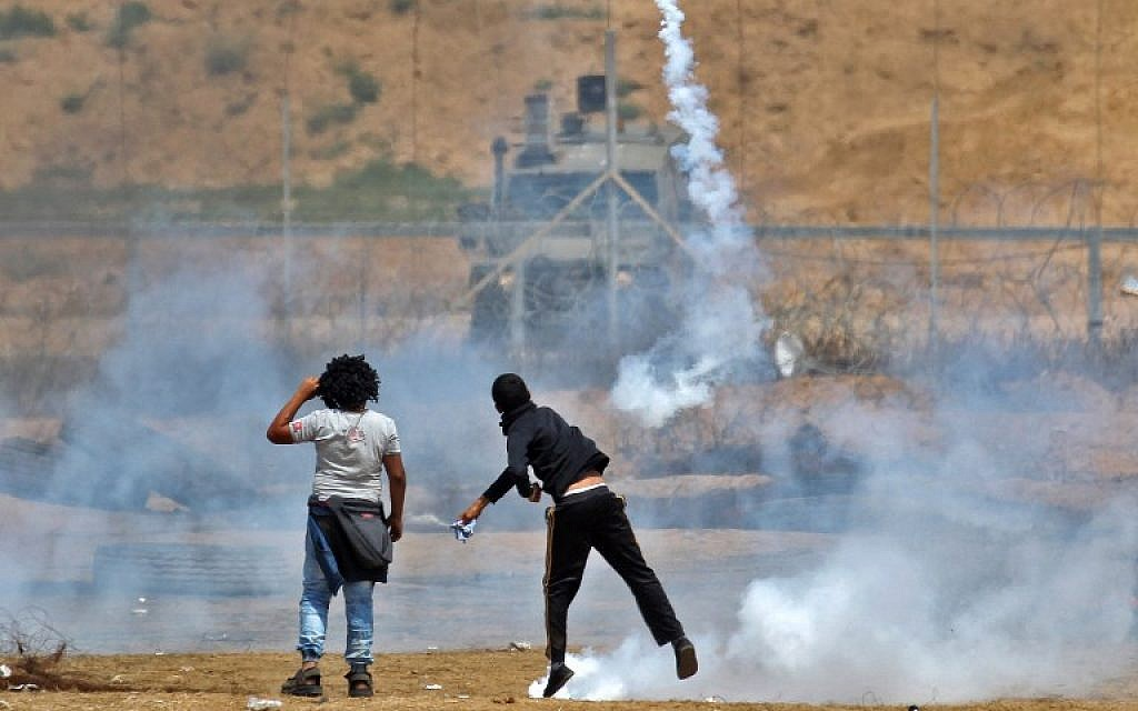 A Palestinian demonstrator throws a tear gas canister back towards Israeli troops near Khan Younis in the southern Gaza Strip, during the fifth straight Friday of mass riots along the border between Gaza and Israel, on April 27, 2018. (AFP Photo/Said Khatib)