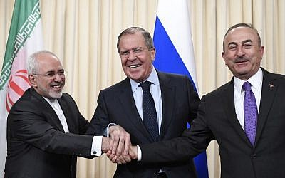 Russian Foreign Minister Sergei Lavrov (C), his Iranian counterpart Mohammad Javad Zarif (L) and Turkish Foreign Minister Mevlut Cavusoglu shake hands at the end of a joint press conference following their talks in Moscow on April 28, 2018. (AFP PHOTO / Alexander NEMENOV)