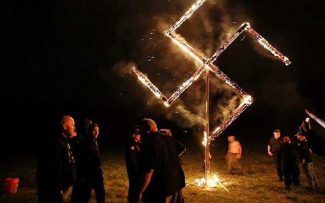 Members of the National Socialist Movement, one of the largest neo-Nazi groups in the US, hold a swastika burning after a rally on April 21, 2018 in Draketown, Georgia. (Spencer Platt/Getty Images/AFP)