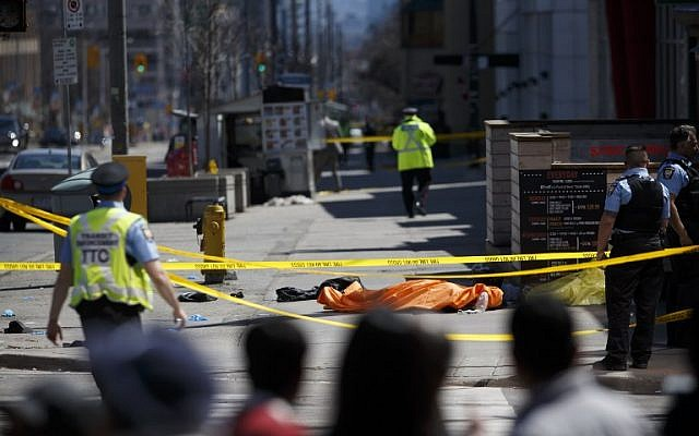 A tarp lays on top of a body on Yonge St. at Finch Ave. after a van plowed into pedestrians on April 23, 2018 in Toronto, Canada. A suspect is in custody after a white van collided with multiple pedestrians.   (Cole Burston/Getty Images/AFP)
