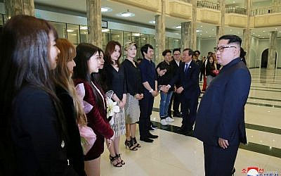 In this photo provided by the North Korean government, North Korean leader Kim Jong Un, right, talks to members of the South Korean artistic group, including the South's pop legends and popular girl band Red Velvet, after their performance in East Pyongyang Grand Theater in Pyongyang, North Korea, April 1, 2018. (Korean Central News Agency/Korea News Service via AP)