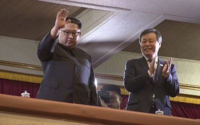 In this April 1, 2018, image from video, North Korean leader Kim Jong Un, left, waves as South Korean Culture, Sports and Tourism Minister Do Jong-whan claps during a performance by a South Korean art troupe in Pyongyang, North Korea.  (Korea Pool via AP)
