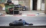 In this Tuesday, April 3, 2018 photo, an African migrant sleeps in a street in southern Tel Aviv. (AP Photo/Ariel Schalit)