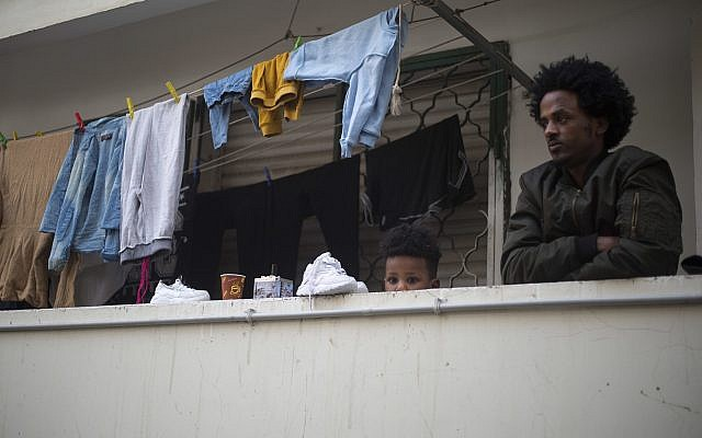 In this Tuesday, April 3, 2018 photo, an African migrant and his son look out of the balcony in southern Tel Aviv. (AP Photo/Ariel Schalit)
