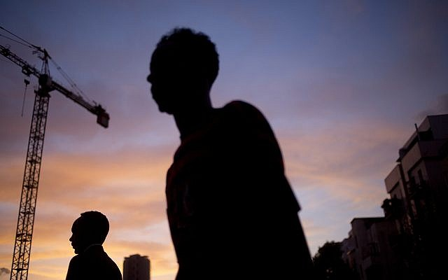 In this Tuesday, April 3, 2018 photo, African migrants cross a street in southern Tel Aviv. (AP Photo/Ariel Schalit)