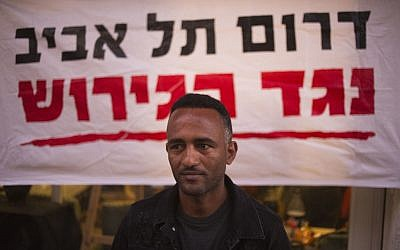 "In this Tuesday, April 3, 2018 photo, Eritrean Halofom Sulta sits under a banner ""South Tel Aviv against deportation"" after speaking to the Associated Press in southern Tel Aviv. (AP Photo/Ariel Schalit)"