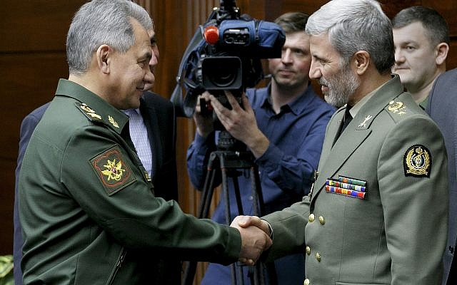 Russian Defense Minister Sergei Shoigu, left, shakes hands with meets with Iranian Defense Minister Amir Hatami during their meeting in Moscow, Russia, Tuesday, April 3, 2018. (Vadim Savitsky/Russian Defense Ministry Press Service via AP)