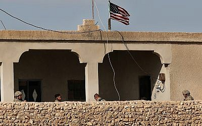 US soldiers, left, sit in a house turned into an outpost on a road leading to the tense front line between US-backed Syrian Manbij Military Council fighters and Turkish-backed fighters, at Halawanji village, north of Manbij town, Syria. (AP Photo/Hussein Malla, File)