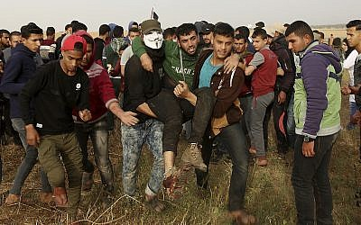 Palestinian protesters evacuate a wounded youth during clashes with Israeli troops along Gaza's border with Israel, east of Khan Younis, Gaza Strip, April 5, 2018. (AP Photo/Adel Hana)