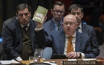 Russian Ambassador to the United Nations Vassily Nebenzia holds up a copy of 'Alice's Adventures in Wonderland' as he speaks during a Security Council meeting on the situation between Britain and Russia on April 5, 2018 at United Nations headquarters in New York. (AP Photo/Mary Altaffer)