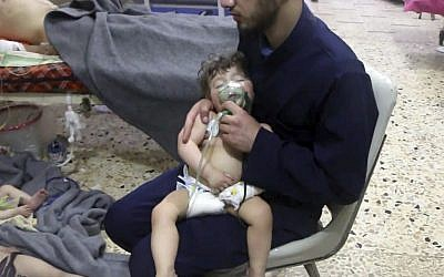 This image made from video released by the Syrian Civil Defense White Helmets, which has been authenticated based on its contents and other AP reporting, shows medical workers treating toddlers following an alleged poison gas attack in the opposition-held town of Douma, in eastern Ghouta, near Damascus, Syria, April. 8, 2018. (Syrian Civil Defense White Helmets via AP)