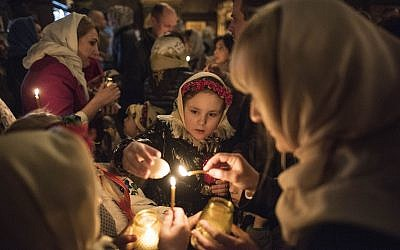 Ukrainian Orthodox believers light candles from the Holy Fire during Orthodox Easter celebrations in the Volodymyrskiy Monastery in Kiev, Ukraine, April 7, 2018. (AP Photo/ Evgeniy Maloletka)