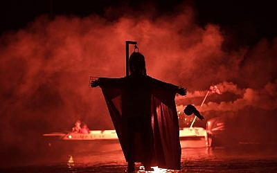 "People on a boat hold flares as they sail behind the effigy of Judas during the revival of the old Easter tradition of the ""burning of the Judas,"" in the port town of Ermioni, in the Peloponnese peninsula, southwest of Athens, April 8, 2018. (AP Photo/Petros Giannakouris)"