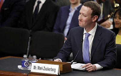 Facebook CEO Mark Zuckerberg reacts to a question about the hotel he stayed in the night before as he testifies before a joint hearing of the Commerce and Judiciary Committees on Capitol Hill in Washington, Tuesday, April 10, 2018, about the use of Facebook data to target American voters in the 2016 election. (AP Photo/Alex Brandon)