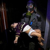 This Sunday, April. 8, 2018 image released by the Syrian Civil Defense White Helmets, shows a rescue worker carrying a child following an alleged chemical weapons attack in the rebel-held town of Douma, near Damascus, Syria. (Syrian Civil Defense White Helmets via AP)