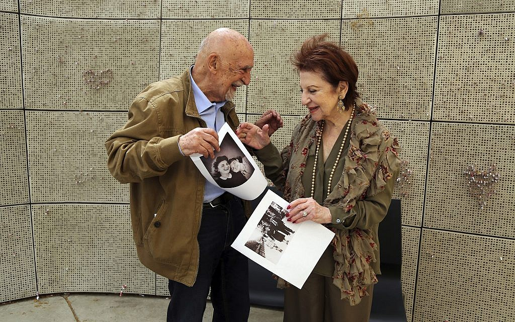 In this Wednesday, April 11, 2018, photo, childhood Holocaust survivors Simon Gronowski and Alice Gerstel Weit exchange photographs they haven't seen in decades, at the Los Angeles Holocaust Museum memorial. (AP Photo/Reed Saxon)
