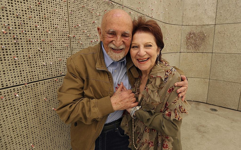 In this Wednesday, April 11, 2018, photo, childhood Holocaust survivors Simon Gronowski and Alice Gerstel Weit hug at the Los Angeles Holocaust Museum memorial. (AP Photo/Reed Saxon)