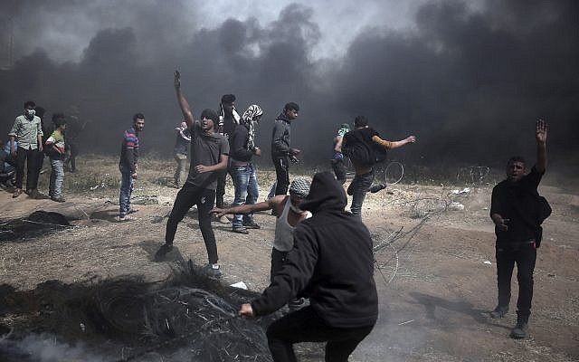 Palestinian protesters hurl stones at Israeli troops at the Gaza Strip's border with Israel, Friday, April 13, 2018. (AP Photo/ Khalil Hamra)