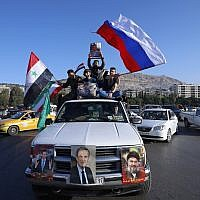 Syrian government supporters wave Syrian, Iranian and Russian flags as they chant slogans against US President Trump during demonstrations following a wave of US, British and French military strikes to punish President Bashar Assad for suspected chemical attack against civilians, in Damascus, Syria, April 14, 2018. (AP Photo/Hassan Ammar)