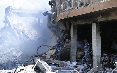 Firefighrers extinguish smoke that rises from the damage of the Syrian Scientific Research Center which was attacked by US, British, and French military strikes to punish President Bashar Assad for suspected chemical attack against civilians, in Barzeh, near Damascus, Syria, April 14, 2018. (AP Photo/Hassan Ammar)