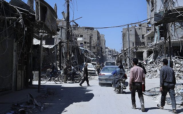 People walk among damaged buildings in the town of Douma, the site of a suspected chemical weapons attack, near Damascus, Syria, on April 16, 2018. (AP Photo/Hassan Ammar)