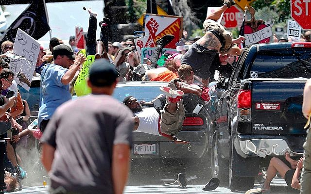 In this August 12, 2017, photo people fly into the air as a car drives into a group of protesters demonstrating against a white nationalist rally in Charlottesville, Virginia. (Ryan Kelly/The Daily Progress via AP)