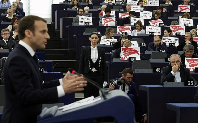 European lawmakers raise placards reading 'Stop the War in Syria' in protest against airstrikes launched by the US, Britain and France in Syria last week, as French President Emmanuel Macron delivers his speech at the European Parliament in Strasbourg, eastern France, April 17, 2018. (AP Photo/ Jean Francois Badias)
