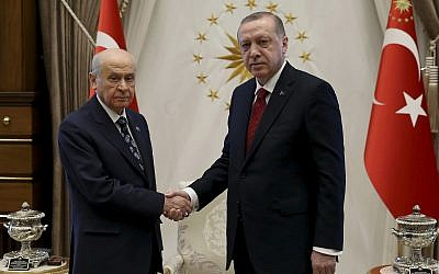 Turkey's President Recep Tayyip Erdogan, right, shakes hands with Devlet Bahceli, leader of the Nationalist Movement Party and his political ally, prior to their meeting, at the Presidential Palace, in Ankara, Turkey, Wednesday, April 18, 2018. (Pool Photo via AP)