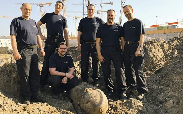 Photo provided by Berlin police Friday, April 20, 2018 shows the bomb squad of the state police Berlin posing behind a bomb from WWII that was found in central Berlin and is planned to be defused on Friday. (Polizei Berlin via AP)