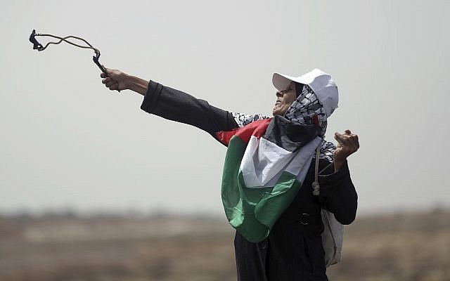 A Palestinian woman hurls stones at Israeli troops during a protest at the Gaza Strip's border with Israel, on April 20, 2018. (AP Photo/ Khalil Hamra)