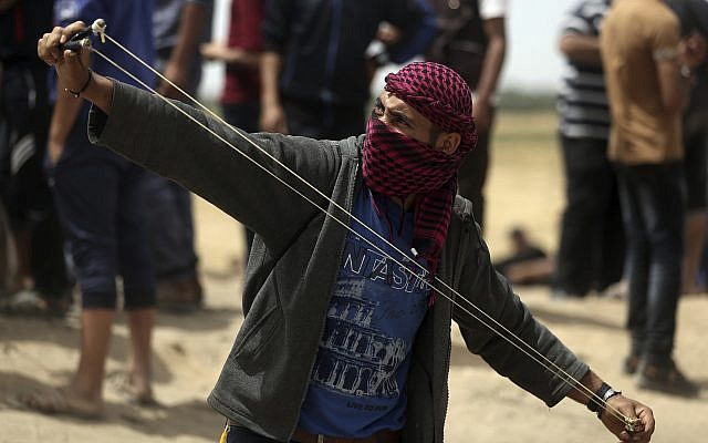 A Palestinian man hurls stones at Israeli troops during a protest at the Gaza Strip's border with Israel, Friday, April 20, 2018.  (AP Photo/ Khalil Hamra)