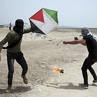 Palestinian protesters fly a kite with a burning rag dangling from its tail, during a protest at the Gaza Strip's border with Israel, April 20, 2018. Activists use kites with burning rags dangling from their tails to set ablaze drying wheat fields on the Israeli side. (AP Photo/ Khalil Hamra)