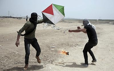 Illustrative: Palestinian protesters fly a kite with a burning rag dangling from its tail, during a protest at the Gaza Strip's border with Israel, April 20, 2018. (AP Photo/Khalil Hamra)