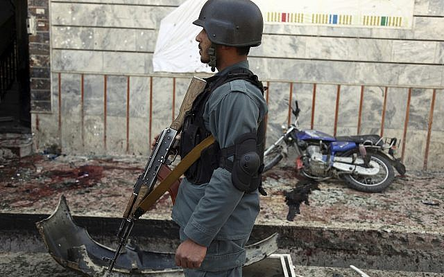 An Afghan police officer stands outside a voter registration center which was attacked by a suicide bomber in Kabul, Afghanistan, Sunday, April 22, 2018. (AP Photo/Rahmat Gul)